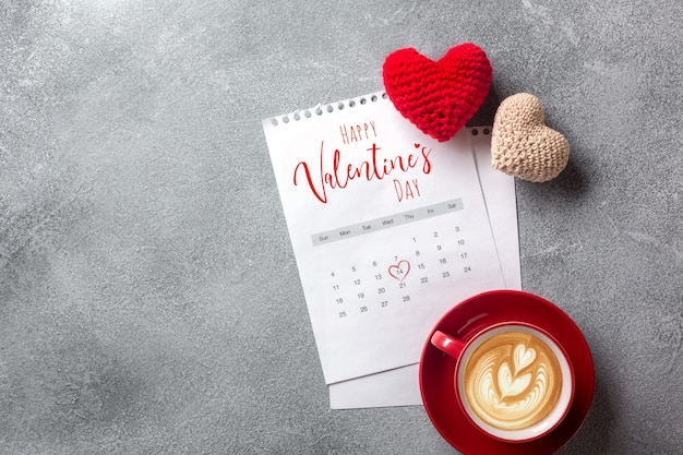 Valentines day greeting card. coffee cup and gift box over february calendar on stone table.