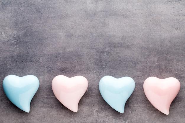 バレンタインデーのグリーティングカード。灰色の背景に色のハート。上からの眺め。フラットレイ。