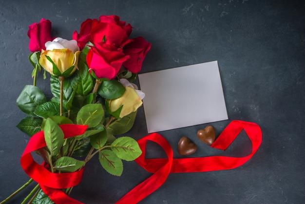 Концепция поздравительной открытки дня святого валентина с цветами красной розы, шампанским, конфетами и подарочной коробкой.