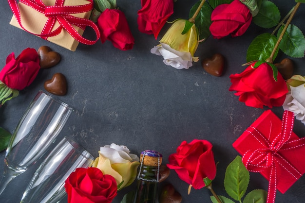 Valentines day greeting card concept with red rose flowers, champagne, chocolates and gift box.