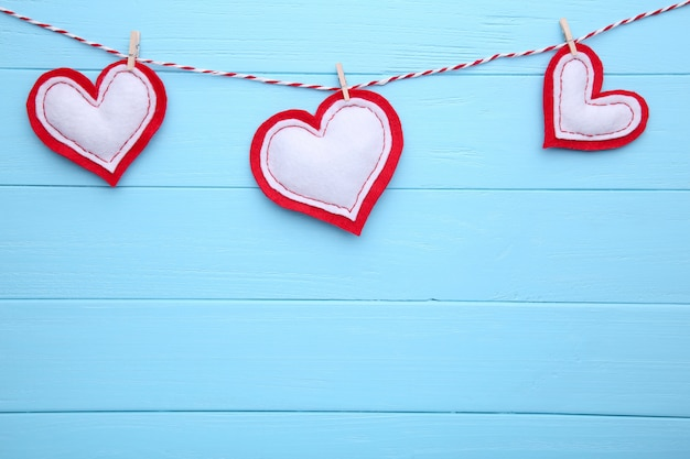 Valentines day greeting card. handmaded hearts on a rope on blue background.