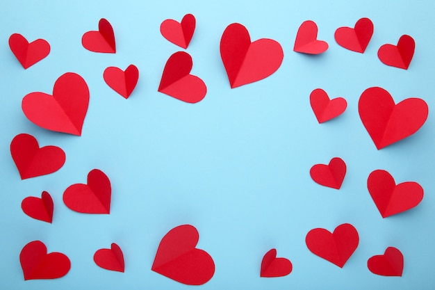 Valentines day greeting card. handmaded red hearts on blue background.
