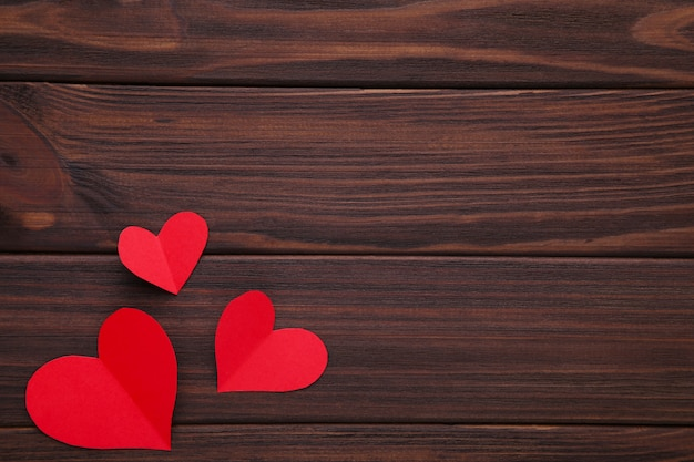 Valentines day greeting card. handmaded red hearts on brown background.