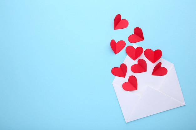 Valentines day greeting card. handmaded red hearts in envelope on blue background.