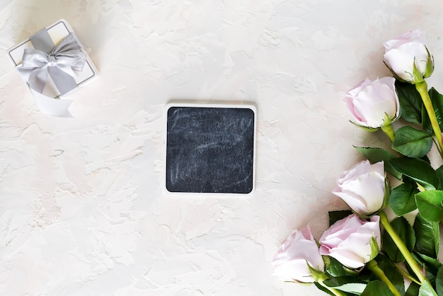 Valentines day greeting card. pink roses and gift box with small chalk boards on light stone , top view with copyspace Premium Photo