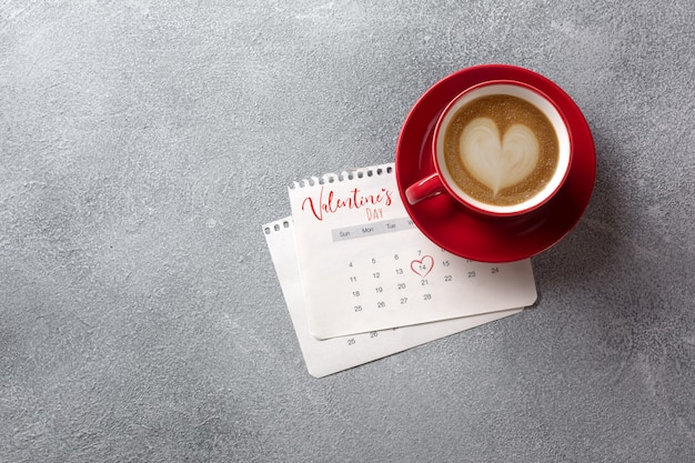 Valentines day greeting card. red coffee cup over february calendar. top view