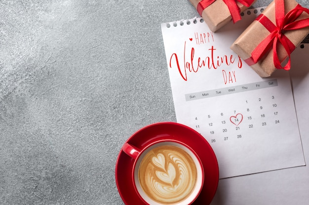 Valentines day greeting card. red coffee cup and gift box over february calendar. top view