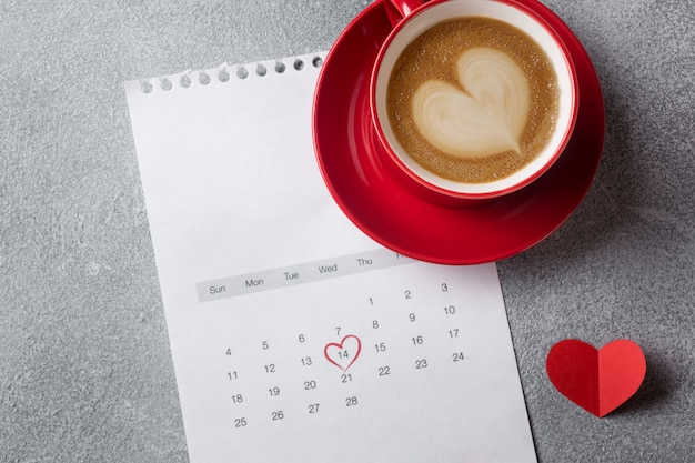 Valentines day greeting card. red coffee cup and gift box over february calendar.