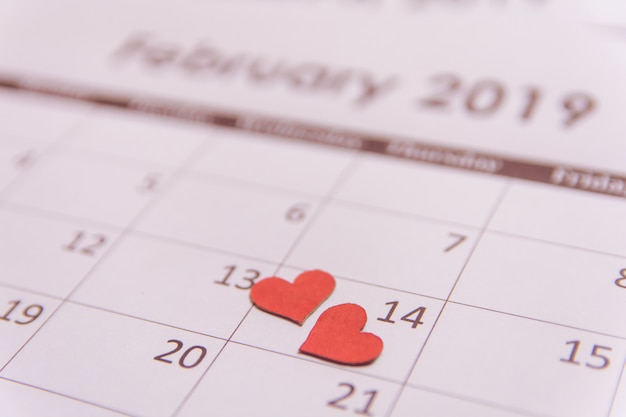 День святого валентина поздравительных открыток. бумага красных сердец на странице календаря 14 февраля с копией пространства