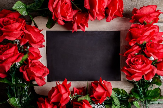 Valentines day greeting card. red rose flowers and chalkboard on wooden table.