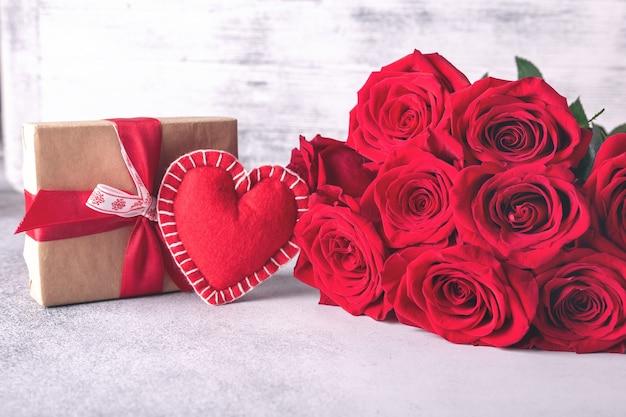 Поздравительная открытка дня святого валентина. красные розы, подарочная коробка и декоративное текстильное сердце на каменном столе. вид сверху.