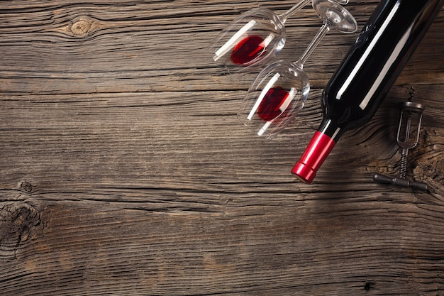 Valentines day greeting card. red wine, gift box and glasses on wooden table. view with space for your greetings.