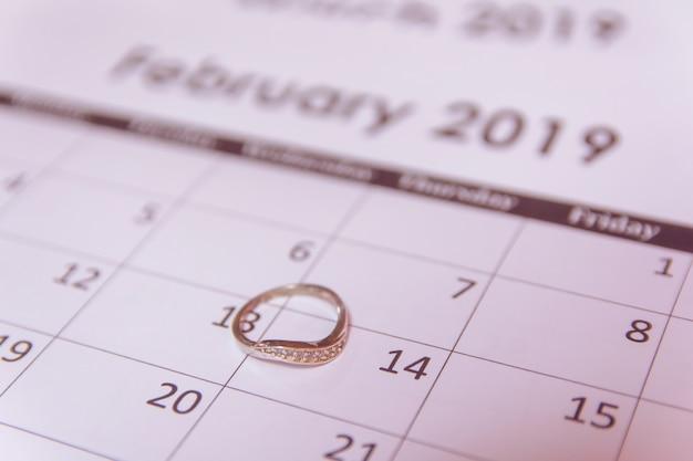 День святого валентина поздравительных открыток. кольцо на странице календаря 14 февраля с копией пространства