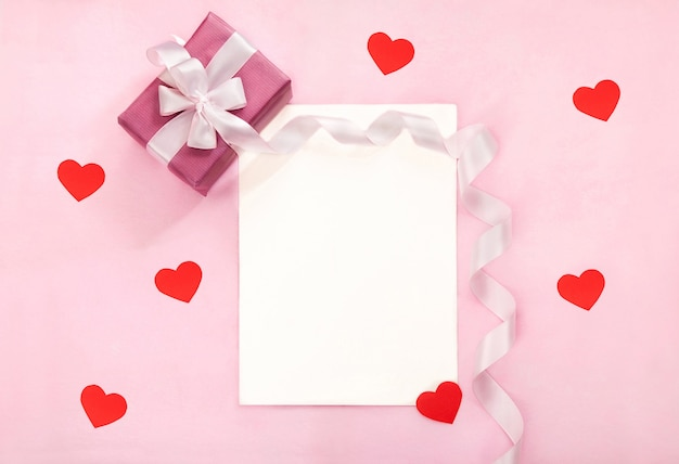 분홍색 선물 상자, 흰 나비, 긴 곡선 리본 및 종이 빨간색 하트 발렌타인 데이 인사말 카드