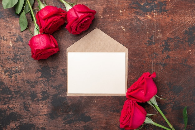 Valentines day greeting card with red roses and envelope on wooden table. top view.