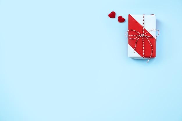青い背景の上のバレンタインデー手作りの包まれたギフトボックス