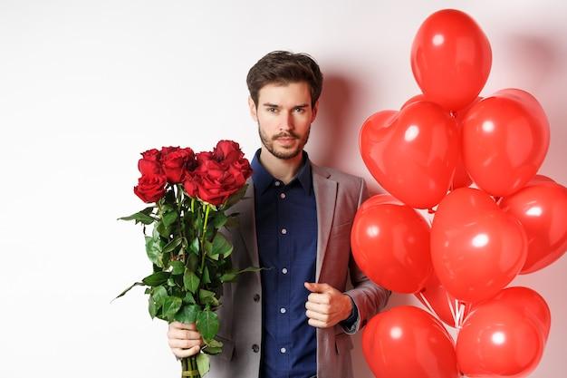 バレンタイン・デー。赤いバラとハートの風船の花束を持って、白い背景に恋人への贈り物を持って立って、スーツを着てデートに行くハンサムで自信のある男。