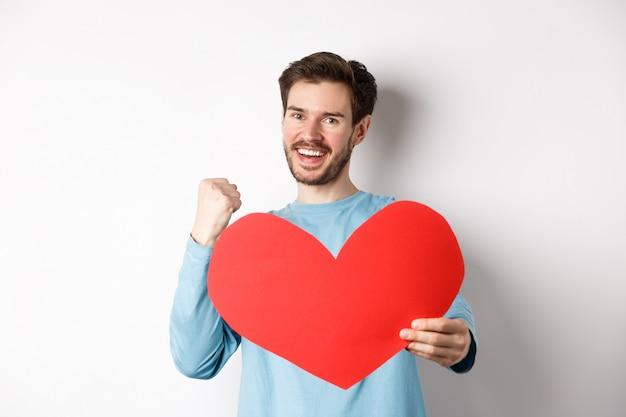 バレンタイン・デー。幸せな彼氏が勝利し、イエスと言ってバレンタインの赤いハートを見せ、勝利の女の子が愛するように笑って、白い背景の上に立って