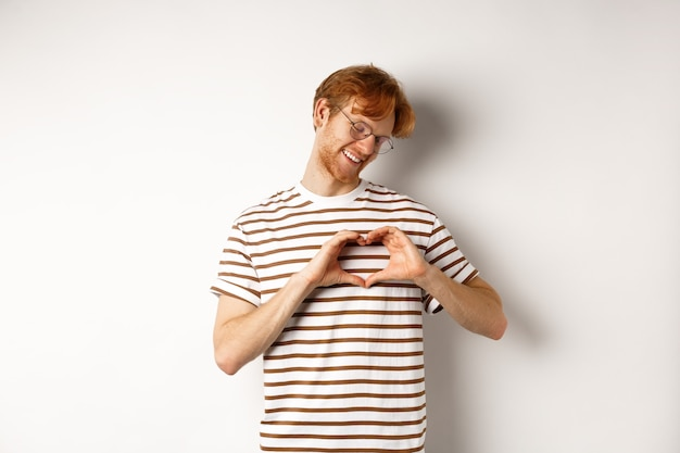 バレンタイン・デー。赤い髪の幸せな彼氏、笑顔と心のジェスチャーを示して、私はあなたを愛して、白い背景の上に立っています。