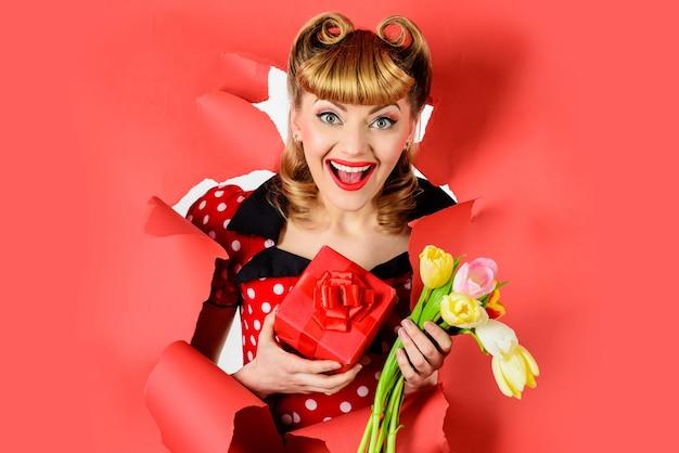 バレンタイン・デー。紙を通して見ている贈り物と花を持つ幸せな女性。プレゼントで女の子をピンで留めます。