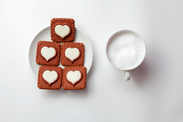 Valentines day heart-shaped cookies and a cup of cappuccino.