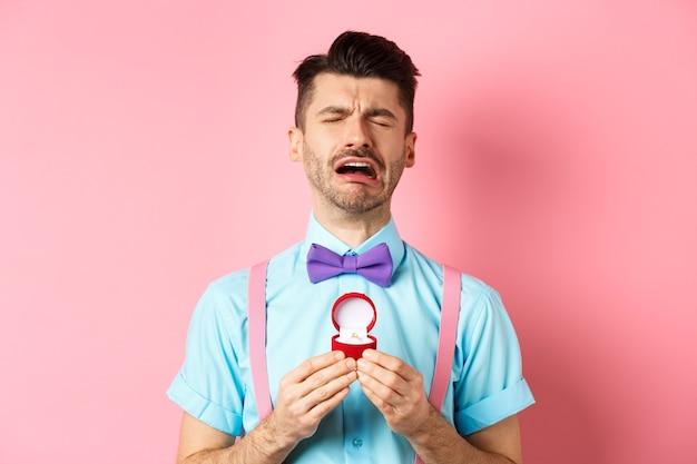 バレンタイン・デー。ピンクの背景の上に立って、別れからすすり泣き、婚約指輪を持って泣いて悲しみに暮れた男。