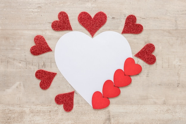 Valentines day hearts with paper on wooden background