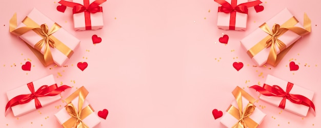 Valentines day holidays border with love decoration gift boxes and on pink background with copy space for text.