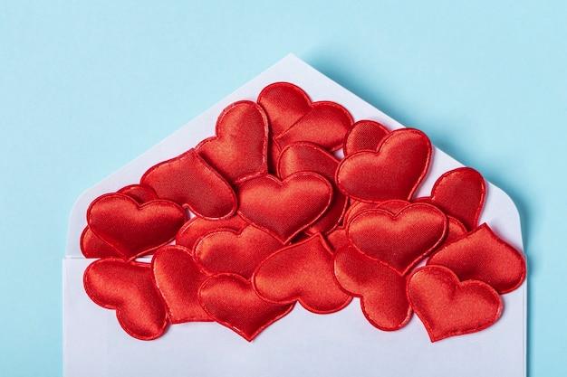 バレンタインデーのレイアウト。赤いハートが青い壁の封筒から注がれています。テンプレート空白のグリーティングカードと結婚式の封筒。フラットレイ、テキスト用のコピースペース