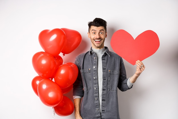 Valentines day and love concept. cheerful funny guy showing heart cutout, standing near romantic balloons and smiling excited at camera, white.
