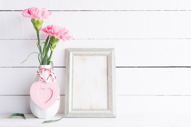 Valentines day, love concept. pink carnation flower in vase with old vintage picture frame