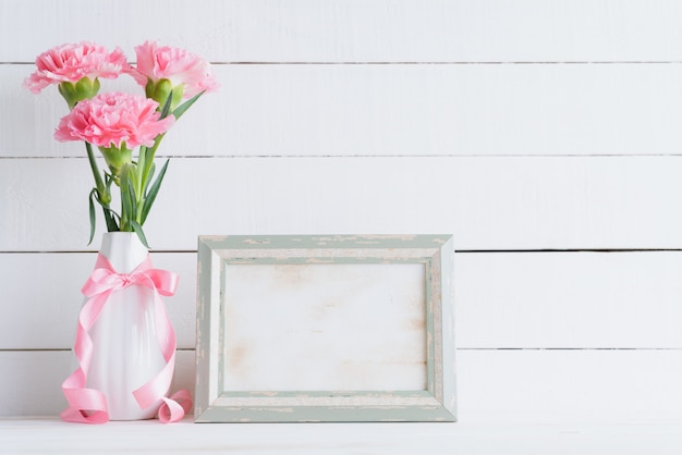 Valentines day and love concept. pink carnation in vase on wooden background.