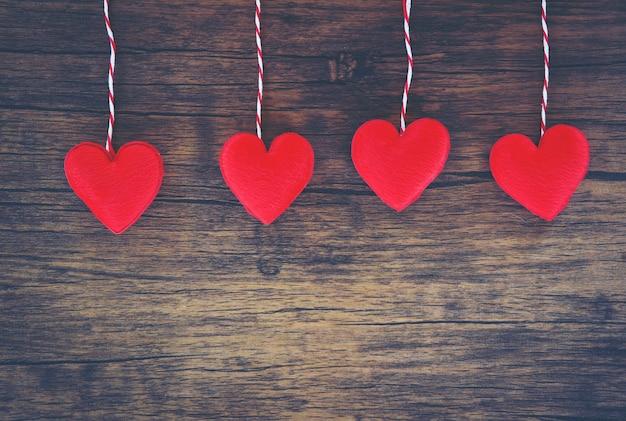 День святого валентина любовь сердце концепция висячие красные сердца украшают на деревянном деревенском текстуру фона