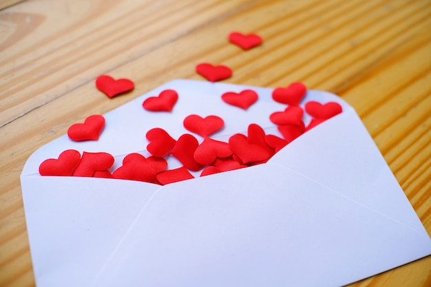Valentines day love letter. opened envelope and many felt hearts. empty copy space.