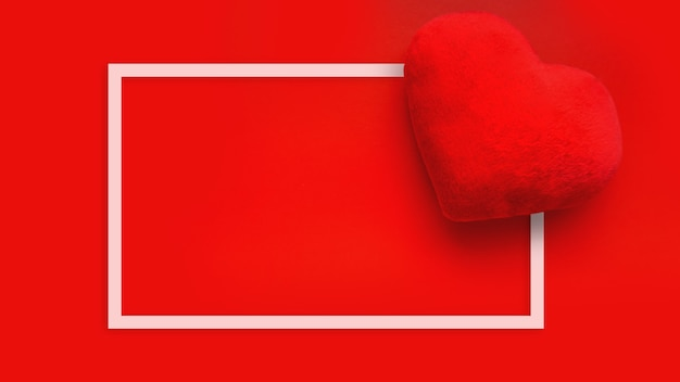 Valentines day love surface with soft toy heart on red surface. top view. for banner, cards design