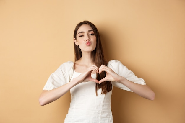 День святого валентина. прекрасная молодая женщина в белом платье, признается в любви, морщит губы для поцелуя и показывает жест сердца любовнику, стоя на бежевом фоне.