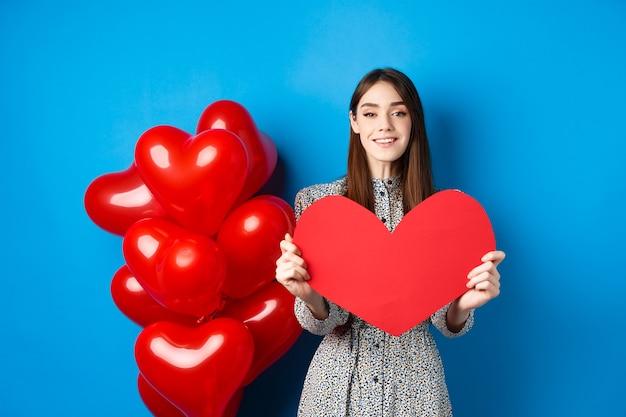 バレンタインカードとsmiを示す恋人たちの休日を祝うドレスを着たバレンタインデーの素敵な若い女性...