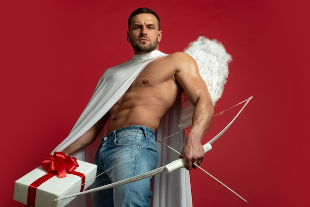 Valentines day man angel. sexy guy with angels wings. cupid. amour. february 14. arrow of love. isolated on red.