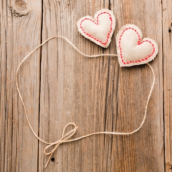 Valentines day ornaments with string on wooden background