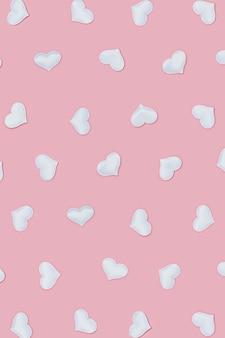 ピンク色の白いハートとバレンタインデーのパターン。パステルカラー。