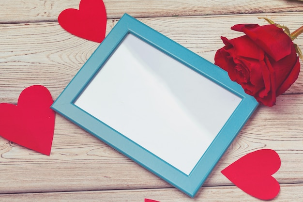 Valentines day photo frame or greeting card and handmaded hearts over table. top view with copyspace