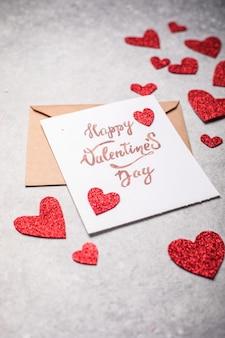 バレンタインデーのポストカード。幸せなバレンタインデーの碑文とヴィンテージコンクリートの灰色の背景に赤いハート