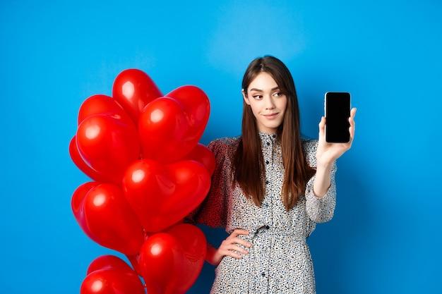 Il giorno di san valentino bella donna sorridente in abito che mostra lo schermo vuoto dello smartphone in piedi vicino a un romantico ...