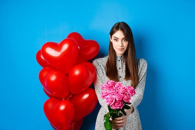バレンタイン・デー。ガールフレンドにロマンチックな贈り物を作るきれいな女性は、美しいピンクの花と笑顔で手を伸ばし、青い背景の上に立っています。