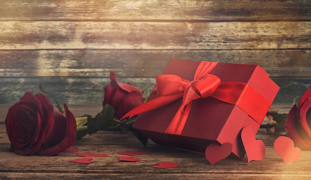 Valentines day. red gift box with red rose and heart on wooden table
