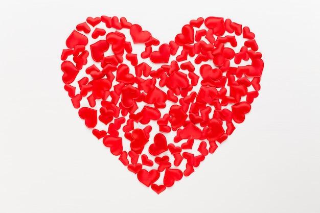 Красные сердца дня святого валентина на белой древесине.