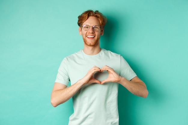 Il giorno di san valentino e il concetto di relazione. fidanzato felice con i capelli e la barba rossi, indossando occhiali e t-shirt, mostrando il segno del cuore e dicendo ti amo, in piedi su sfondo turchese