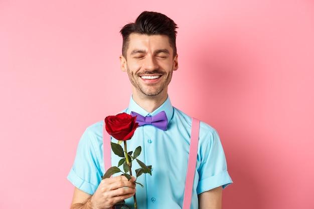 Il giorno di san valentino e il concetto di romanticismo. uomo romantico con rosa rossa che va ad un appuntamento con l'amante, in piedi con un papillon fantasia su sfondo rosa.