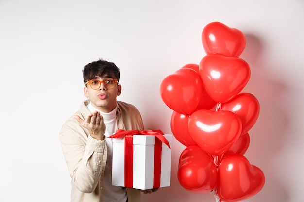 Il giorno di san valentino e il concetto di romanticismo. uomo moderno romantico che tiene un regalo speciale per l'amante e invia un bacio d'aria alla telecamera, in piedi vicino a palloncini di cuori, sfondo bianco.