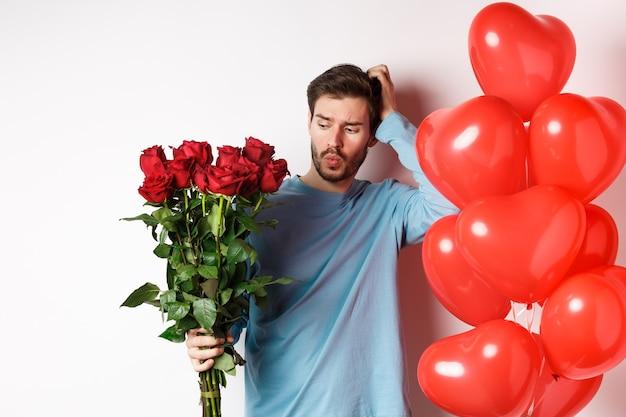 발렌타인 데이 로맨스. 혼란스러운 남자친구는 머리를 긁적이며 데이트를 위해 빨간 장미 꽃다발을 보고 있습니다. 우유부단한 느낌의 꽃과 풍선을 가진 남자, 흰색 배경
